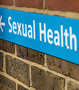 A sign showing the directions to a sexual health clinic